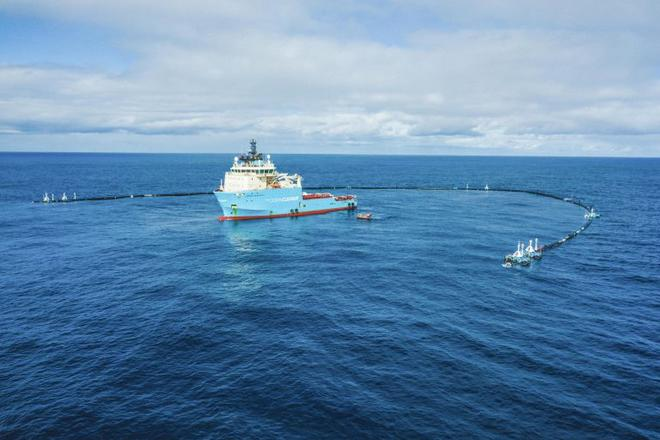 Ship of The Ocean Cleanup in the ocean with the first version of the cleanup system.